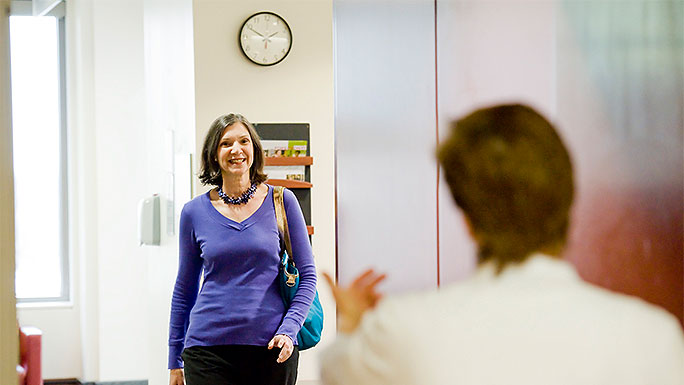 Woman greeted by team member while walking from waiting room